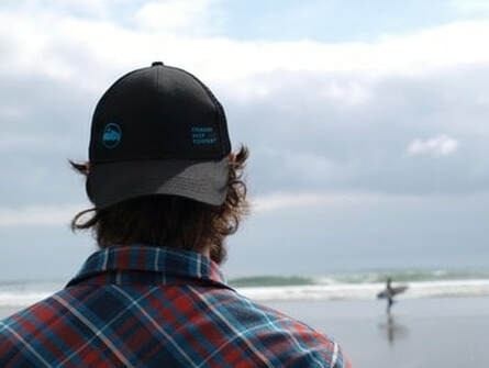A man looking out at the horizon over a body of water; he's got a backwards baseball cap on & tartan button up