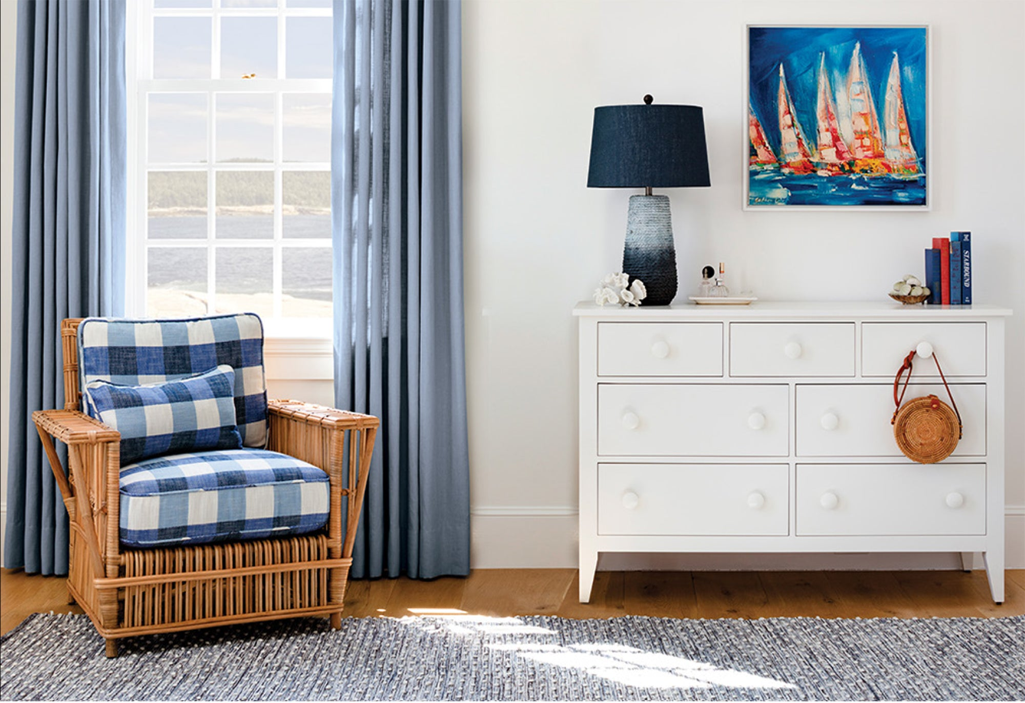 Room with white dresser and blue accents: wicker chair with denim cushions, Marlow lamp, indoor/outdoor rug, Regatta artwork