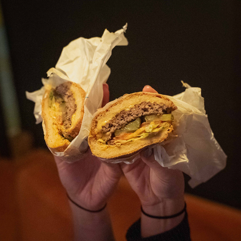 best burgers in Leeds: two hands each holding half a burger and doing a cheers action with them