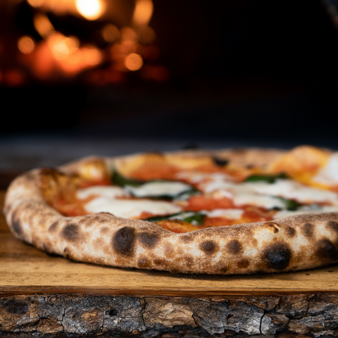 Best Pizza in Leeds: a close up of a whole pizza on a wooden board, with a fired up pizza oven out of focus in the background. The crust is slightly charred in places and the cheese is beautifully melted.