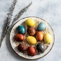A bowl of coloured eggs on a blue background