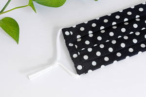 Close up of Pleated Cotton cloth face mask, White Polka Dots on Black Ground