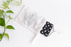 Ivory cotton cloth pouch with printed logo stating 100% hand made and containing one folded mask