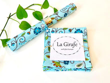 Load image into Gallery viewer, One rolled and one folded napkins with a Floral pattern on Blue ground