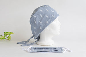 Side view of Cloth scrub hat with White Flamingo pattern on light Grey with a matching face mask