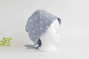 Side view of Cloth scrub hat with White Flamingo pattern on light Grey ground