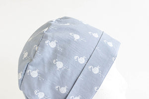 Close up of Cloth scrub hat with White Flamingo pattern on light Grey ground