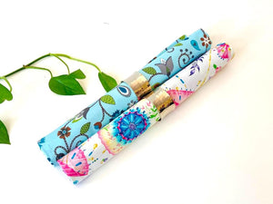 One rolled napkin with a Japanese Umbrellas pattern and one with a Blue Floral pattern