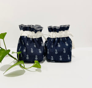 Two Pouches made of Denim with Pineapple pattern with a stack of white makeup remover pads