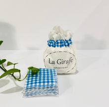 Load image into Gallery viewer, Ivory pouch printed with La Girafe Couture logo with a stack of Blue Checkered makeup remover pads