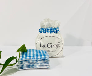 Ivory pouch printed with La Girafe Couture logo with a stack of Blue Checkered makeup remover pads
