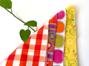 Four flat towels with Plaids, Circles and Floral patterns in bright Pink, Orange, Yellow and Green