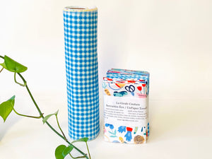 A stack of folded towels with Butterfly, Checks and Garden patterns with a rolled towel