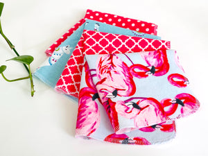 Four folded towels with Flamingo, Lamas and Polka Dots patterns in Pink and Blue