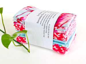 A stack of folded towels with Flamingo, Lamas and Polka Dots patterns in Pink and Blue