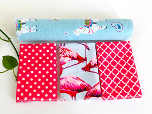 Three folded and one rolled towels with Flamingo, Lamas and Polka Dots patterns in Pink and Blue