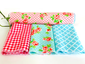 Three folded and one rolled towels with Roses and Checks patterns in Blue and Pink