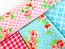 Load image into Gallery viewer, Closeup of three folded and one rolled towels with Roses and Checks patterns in Blue and Pink