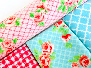 Closeup of three folded and one rolled towels with Roses and Checks patterns in Blue and Pink