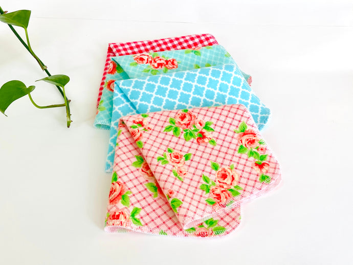 Four folded towels with Roses and Checks patterns in Blue and Pink