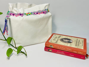 One big bag in off-white cotton canvas with a Butterfly trim next to a book