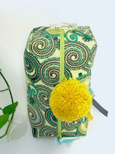 Load image into Gallery viewer, Top view of rectangular Cosmetic bag with Green Paisley printed pattern and Yellow Pompon