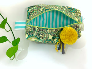 Top view of rectangular Cosmetic bag with Green Paisley printed pattern and Yellow Pompon