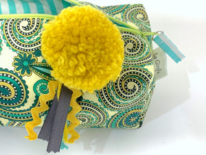 Closeup of rectangular Cosmetic bag with Green Paisley printed pattern and Yellow Pompon