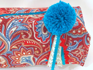 Closeup view of rectangular cloth cosmetic bag with zipper, Red Paisley pattern and Blue Pompon