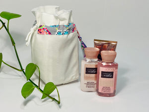 One small bag in off-white cotton canvas with a Butterfly trim next to 3 small bottles of lotion