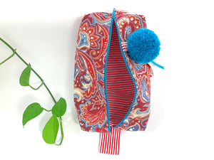 Top  view of rectangular cloth cosmetic bag with zipper, Red Paisley pattern and Blue Pompon