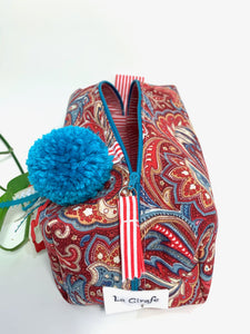 Top front view of rectangular cloth cosmetic bag with zipper, Red Paisley pattern and Blue Pompon