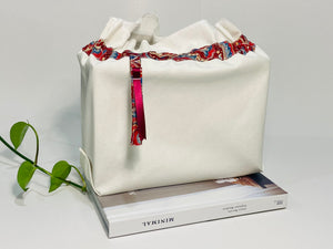 One big bag in off-white cotton canvas with a Red Paisley trim next to a book