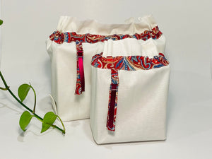 Two bags in off-white cotton with a Red Paisley trim. One bag is big and one small.