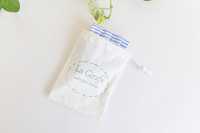 Ivory pouch printed with La Girafe logo and containing one folded face mask