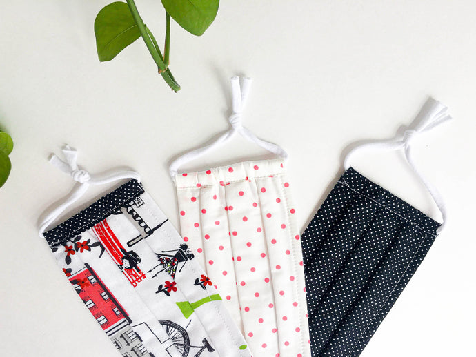 Closeup of Three face mask one Paris Street print one Pink Dots one White Dots on Black