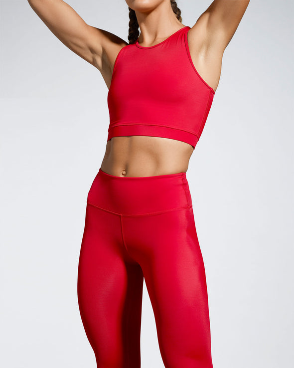 Model wearing Scultura Activewear. Red sustainable Debutto Gym crop in sporting red. Racer back crop design with high scoop neckline. Made with super soft premium sports wear fabric created from ECONYL® regenerated yarn. Hand made in our ethically compliant factory in London. Made in the UK.  Front view