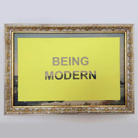 "Framed artwork by Nicolas Vander Beist. Yellow rectangle with ""BEING MODERN"" cut out."