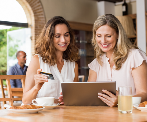 Two ladies at a coffee place, smiling and looking at a tablet, one of them holding on a credit card, ready to pay online