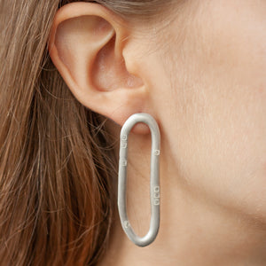 PARAGON COIL silver mismatched earrings  on a model | Margo Orlovik IMPRINT Collection Contemporary Jewellery