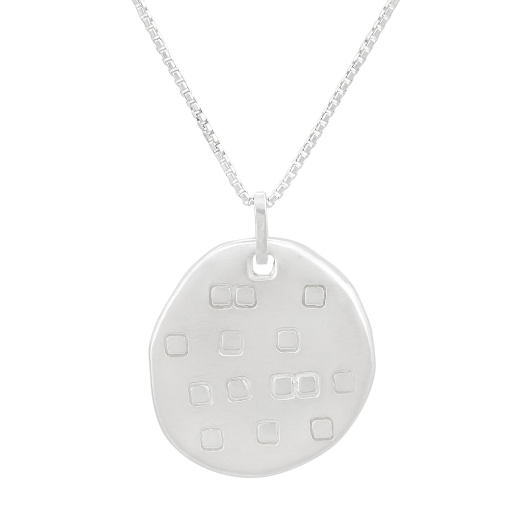 Organic shaped silver pendant with square pattern, on a chain.