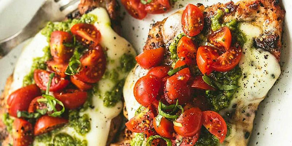 Baked Caprese Chicken Pesto with Cherry Tomatoes and Mozzarella Cheese