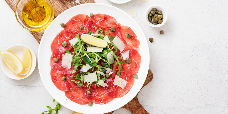 Beef carpaccio with arugula, cheese shavings, and capers