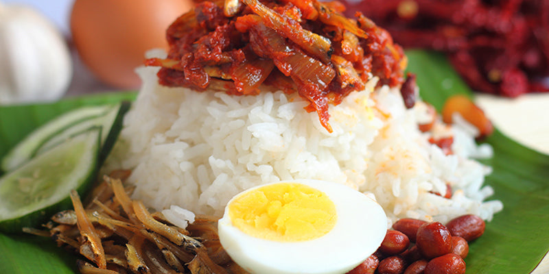 Malaysian Breakfast Nasi Lemak Coconut Rice with Anchovies, Hard Boiled Egg, and Indonesian Chili Paste