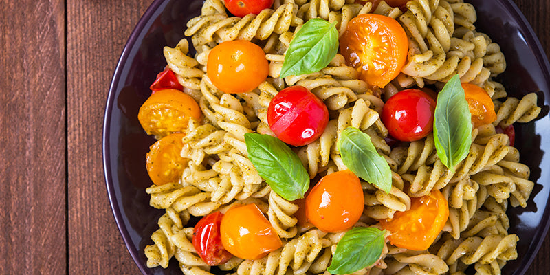 Fusilli pesto pasta salad with red and yellow tomatoes and fresh basil