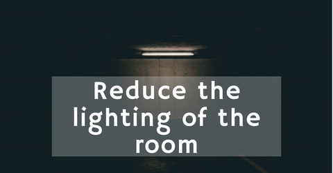 Reduce the lighting of the room