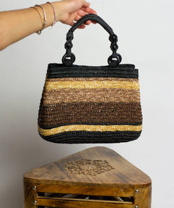 Girl's hand holding neutral straw bag with black beads on the handles