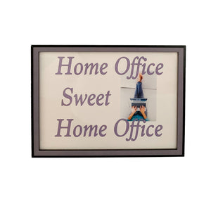 Cute home office sign depicting woman lying down with a laptop. Framed in black rimmed lavender wood frame