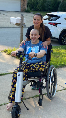 a young man and a woman pose behind the Companion, a scooter-like device attached to the front of his wheelchair