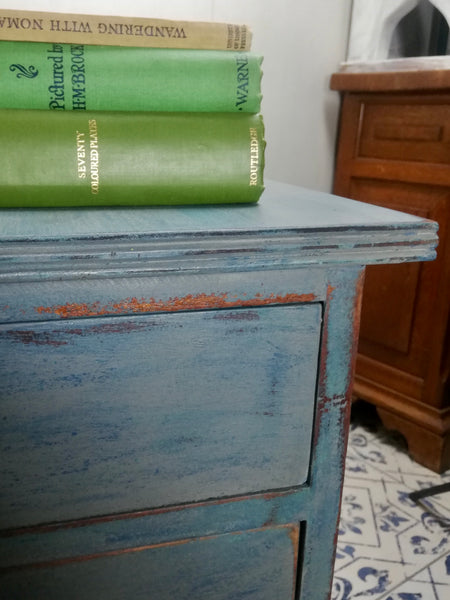 Vintage wooden filing cabinet painted in chippy layers of blue and grey.